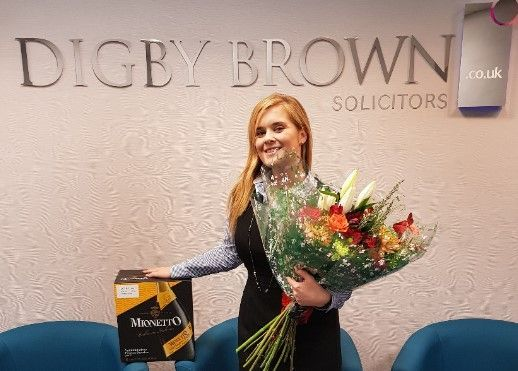 Jennifer Watson, Dundee Personal Injury Solicitor, with bouquet of flowers and case of prosecco from client