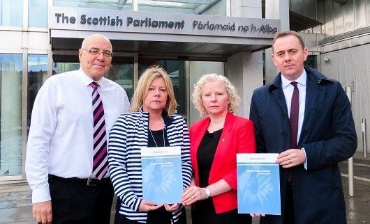 John Fearn and Dianne Foster from Asbestos Action, MSP Claire Baker and Euan Love from Digby Brown outside The Scottish Parliament