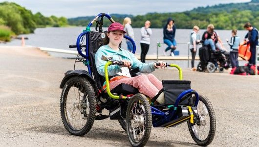 Spinal injury patient on hand bike at SIS BBQ and Activities Day 2019
