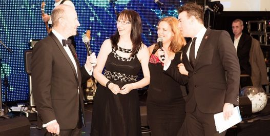 Comedian Fred MacAulay and Des Clarke on stage at the Winter Dinner Dance with winners of Vauxhall Viva