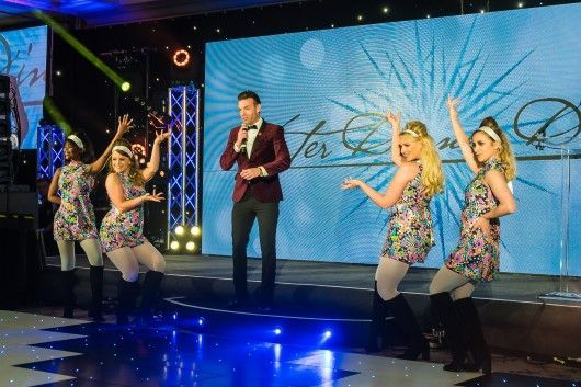 Des Clarke with dancers on stage at the Digby Brown Winter Dinner Dance 2019